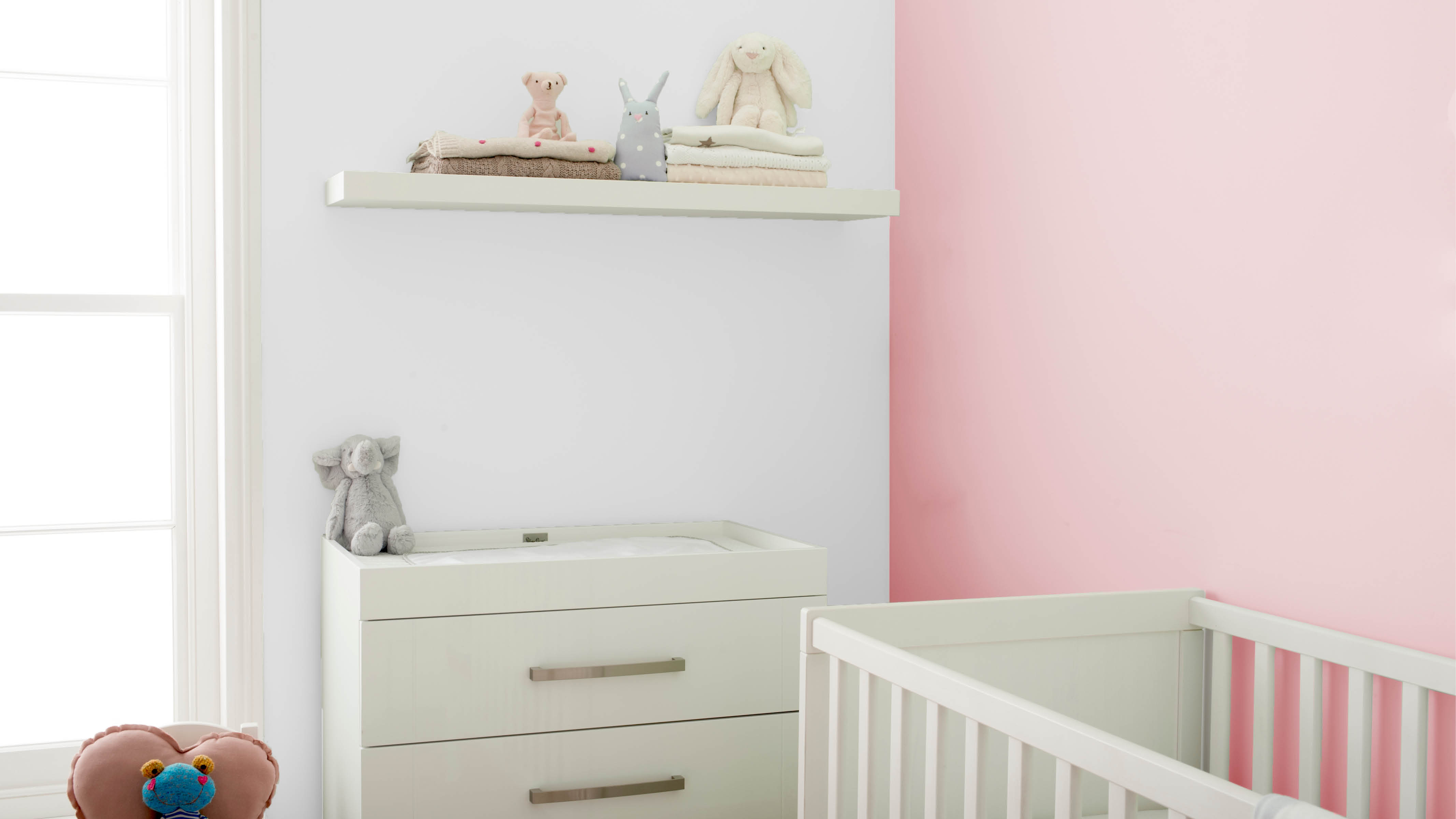 A white cabinet and a set of floating shelves are a great place to stash nappies and other baby care items.