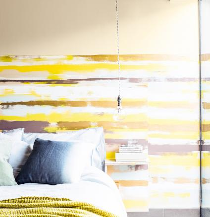 Express your creativity with this striking striped feature wall. This easy DIY project is as simple as layering contrasting hues create a bold, blurred paint effect.